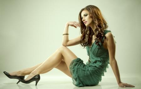 pretty brunette wearing green fashion dress on light background