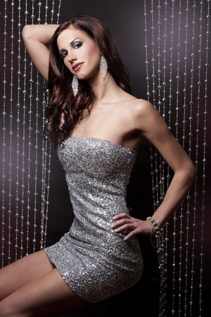 pretty brunette wearing silver party dress on black background photo