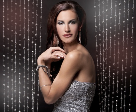 pretty brunette wearing silver party dress on black background Stock Photo - 13222783