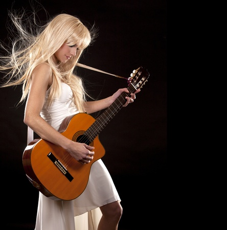 pretty blond in corset playing guitar on black background