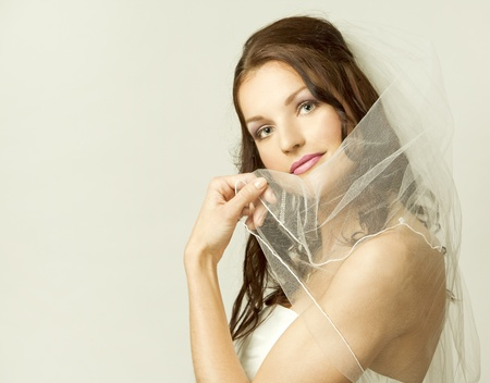 pretty brunette wearing wedding dress on light background photo