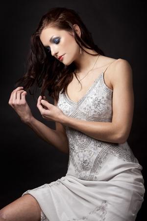 pretty brunette wearing grey fashion dress on black background photo