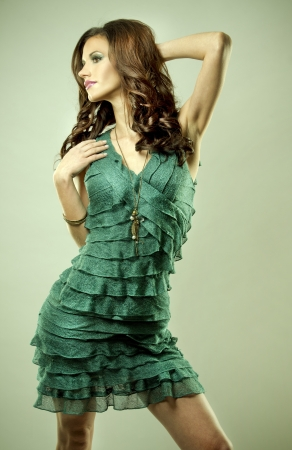 pretty brunette wearing green fashion dress on light background photo