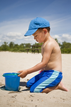 boy toddler is playing with sand on the beach