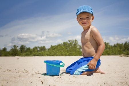 boy toddler is playing with sand on the beach  photo