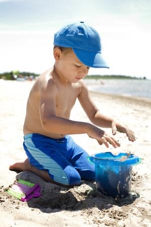 playing in the sea: boy toddler is playing with sand on the beach