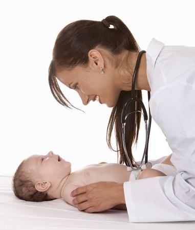 Ärztin Überprüfung Baby auf weißem Hintergrund isoliert