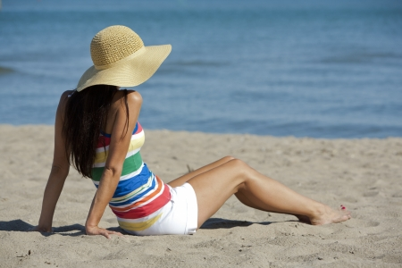 beach wear: pretty brunette sitting in the sand on the beach Stock Photo