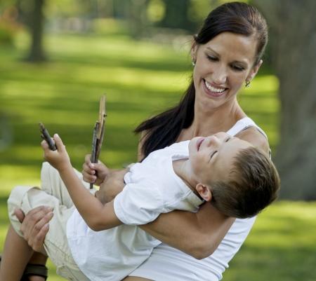 madre e hijo: joven madre jugando con su hijo en el parque Foto de archivo