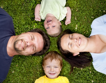 mother, father, son and daughter having fun on the grass Stock Photo - 14886185