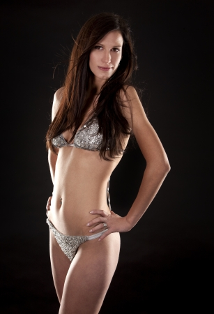 pretty brunette wearing silver bikini on black background photo