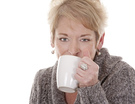 casual blond woman in her fifties holding white cup photo