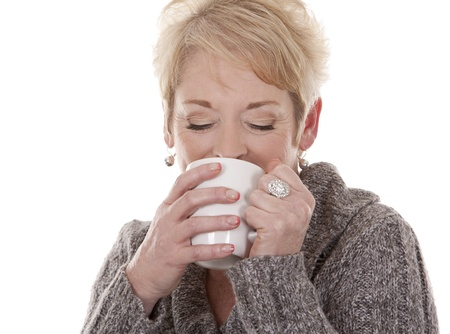 winter woman: casual blond woman in her fifties holding white cup
