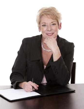 mujeres mayores: mujer madura sentada detrás del escritorio y escribiendo notas abajo