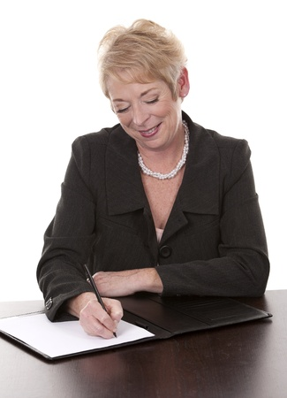 mature woman sitting behind desk and writing notes down Stock Photo - 15358188