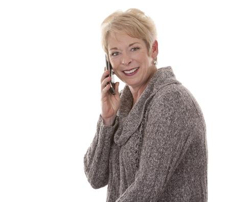 toevallige blonde vrouw van in de vijftig met telefoon op witte achtergrond geà ¯ soleerd