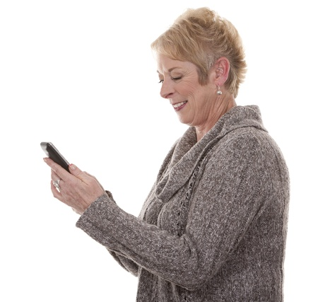 casual blond woman in her fifties using phone on white isolated background photo