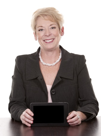 old people: mature woman sitting behind desk and holding tablet