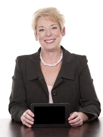 volwassen vrouw zitten achter een bureau en houdt tablet