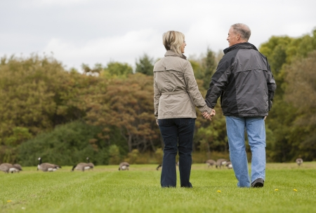 older casual couple sitting in the grass outdoors Stock Photo - 15562607