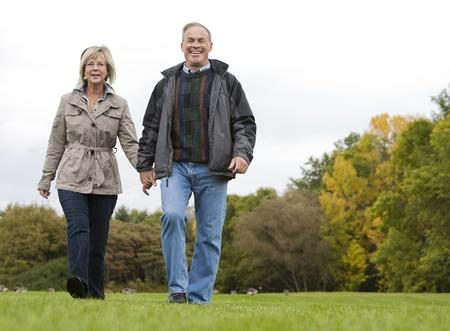 senioren wandelen: ouder casual paar zittend in het gras buiten