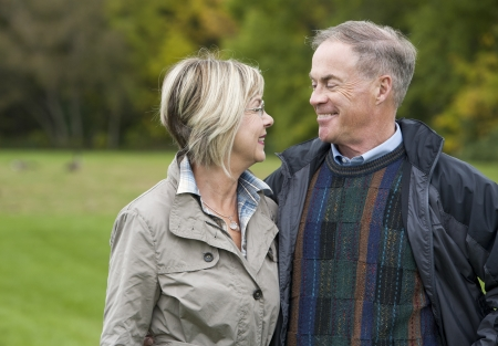 older casual couple sitting in the grass outdoors Stock Photo - 15562825