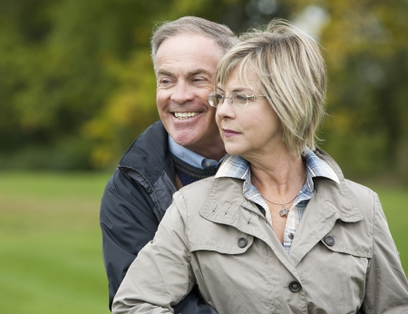 60s adult: older casual couple sitting in the grass outdoors