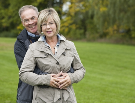 older casual couple sitting in the grass outdoors Stock Photo - 15562810