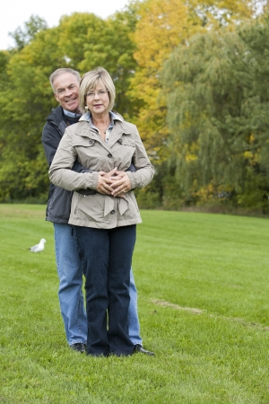 older casual couple sitting in the grass outdoors photo