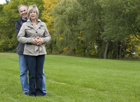 older casual couple sitting in the grass outdoors Stock Photo - 15562832