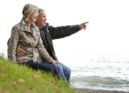 älteren Casual Paar sitzt im Gras im Freien