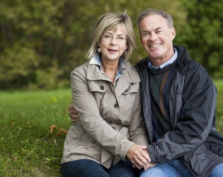 older casual couple sitting in the grass outdoors Stock Photo - 15562805