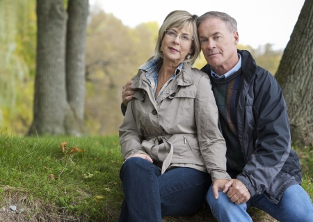 older casual couple sitting in the grass outdoors Stock Photo - 15562792
