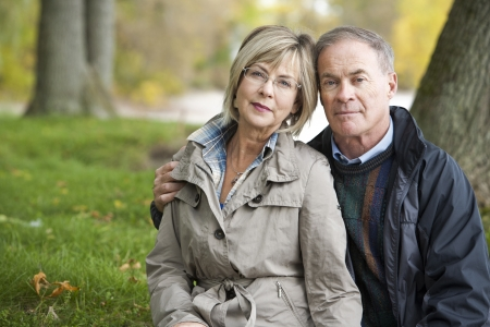 elderly couples: older casual couple sitting in the grass outdoors