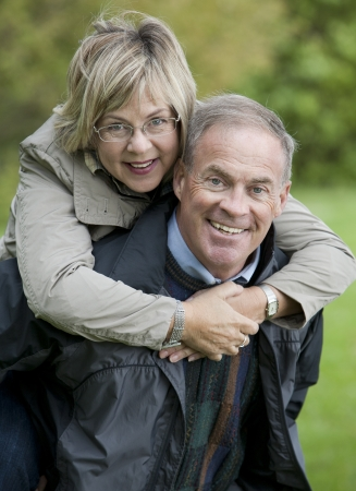 older casual couple sitting in the grass outdoors Stock Photo - 15562820