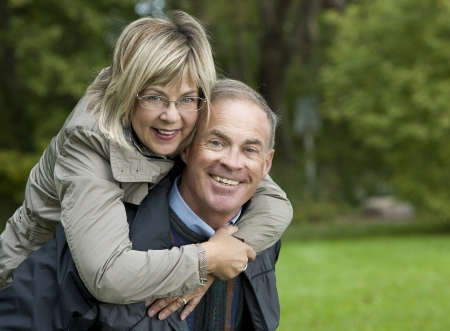 older casual couple sitting in the grass outdoors Stock Photo - 15562807