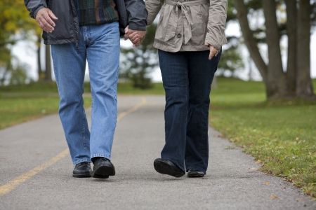 casual couple in their 60s walking together photo