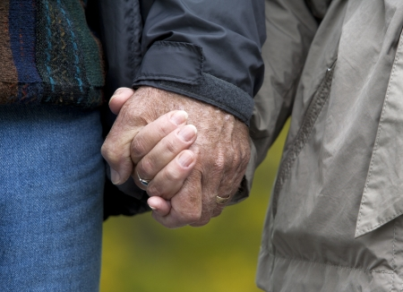 casual couple in their 60s holding hands together photo
