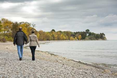 family health: older casual couple walking in the park outdoors