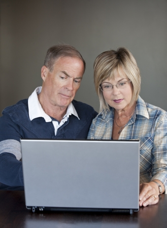 older casual couple sitting and using their laptop photo