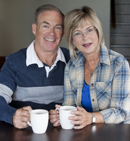 happy senior couple is having coffee together indoors