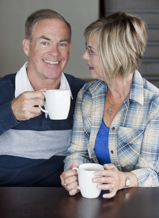 indoors: happy senior couple is having coffee together indoors