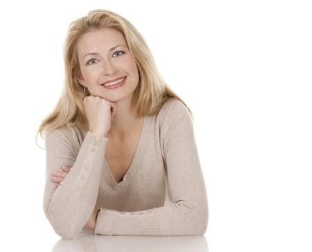 pretty blond woman wearing beige top sitting on white background Standard-Bild