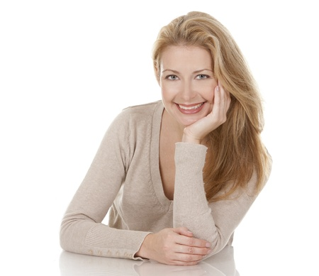 pretty blond woman wearing beige top sitting on white background Stock Photo