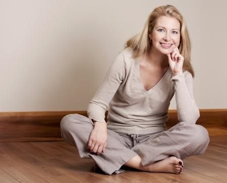 40s adult: pretty blond woman wearing beige top relaxing on the floor Stock Photo