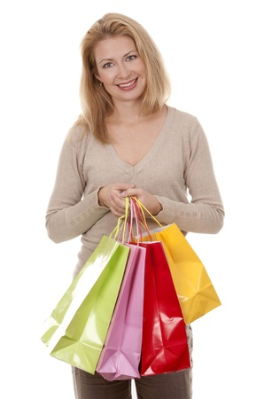 pretty blond woman wearing beige sweather holding shopping bags