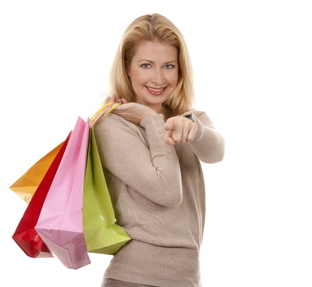 pretty blond woman wearing beige sweather holding shopping bags photo