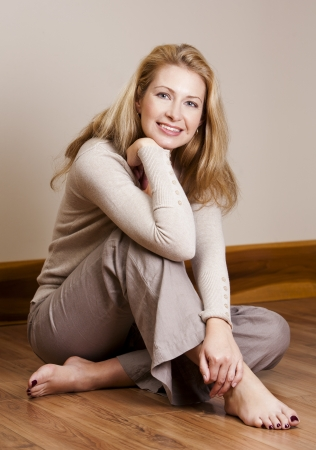 forties: pretty blond woman wearing beige top relaxing on the floor Stock Photo