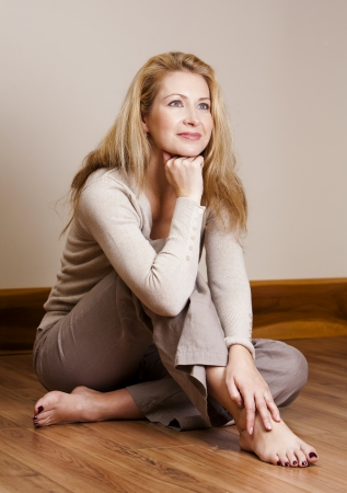 pretty blond woman wearing beige top relaxing on the floor photo
