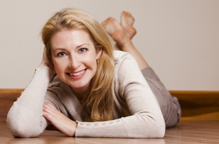sitting down: pretty blond woman wearing beige top relaxing on the floor Stock Photo